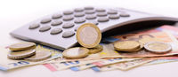 Euro currency with banknotes, calculator and coins