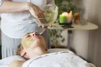 Beautiful relaxed woman having clay face mask in the spa salon