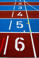Starting numbers on a red and blue striped athletic track