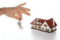 Schlüssel als Symbol mit Haus im Hintergrund