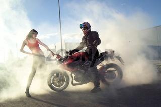Motorradfahrer und Frau im Staub
