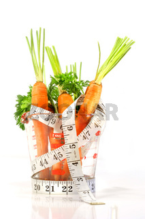 Carrots in a measuring cup with tape measure
