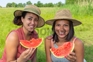 Two women eating fresh melon in nature