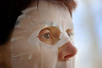 Woman with facial mask sheet