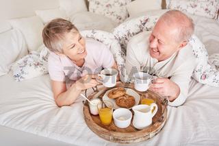 Senioren Paar frühstückt im Bett im Hotel