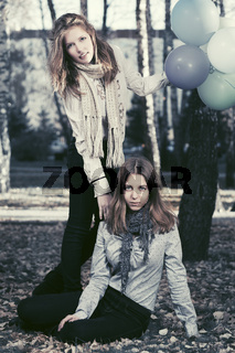 Two fashion teen girls with a balloons in autumn park
