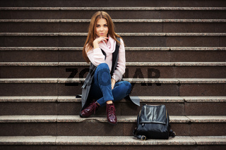 Young fashion woman in grey coat with handbag sitting on the steps