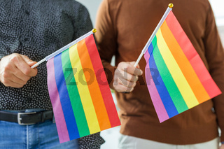 close up of male couple with gay pride flags