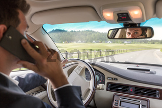 Man talking on cell phone while driving not paying attention to the road.