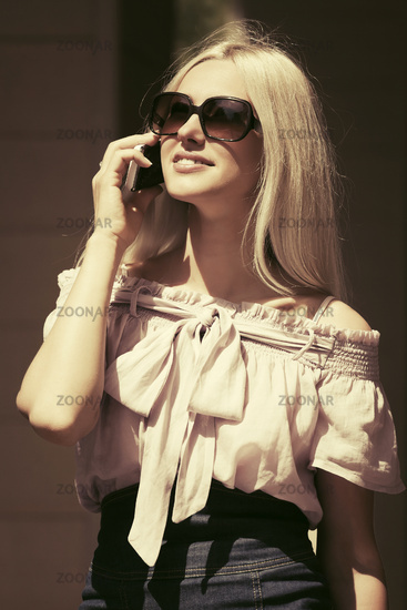 Happy fashion blond woman in sunglasses calling on mobile phone