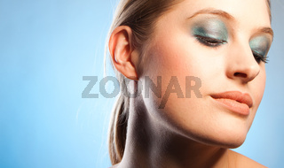 Closeup look of gorgeous young woman with blue makeup on blue background
