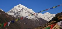 Prayer flags and snow capped Sunder Peak.