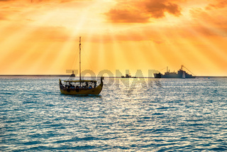 Sunset over blue sea with ship
