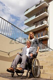 Rollstuhlfahrerin mit Begleitung auf Treppen