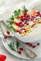 Healthy smoothie bowl of strawberries, pomegranate and almonds.