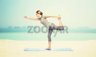 woman making yoga in lord of the dance pose on mat