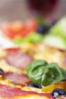 Nahaufnahme einer Pizza mit einem Blatt Basilikum