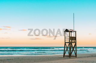 Teal and orange mood of Beach sunrise with vintage lifeguard wooden tower