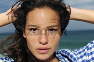 Portrait einer schönen Frau mit Sommersprossen am Strand