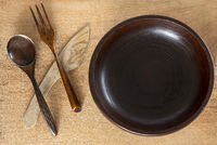 Wooden plate knife, spoon and fork on wooden background