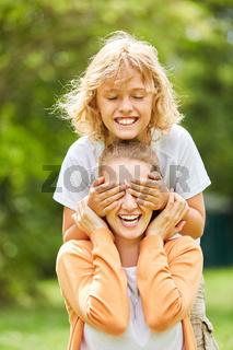 Junge hält seiner Mutter die Augen zu