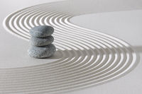 Japanese zen garden with stacked stones in white sand