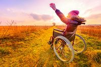 Happy man at sunset. A young girl in a wheelchair - back view