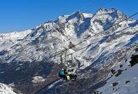 Skifahrer auf dem Längfluh Sesssellift vor Fletschhorn und Lagginhorn