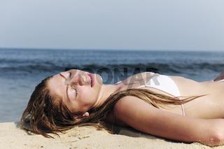 sexy Frau im Bikini liegt im Sand am Strand und entspannt