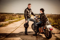 Bikers couple Man and woman near a motorcycle on the road
