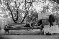 Black and white portrait of homeless man lying on bench.