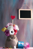 Flower bouquet with gift and blackboard