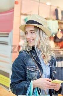 Junge Frau mit Strohhut und Smartphone
