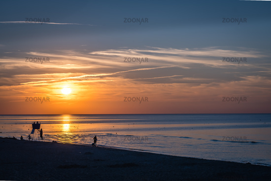 People walking on the  beach in summer at sunset