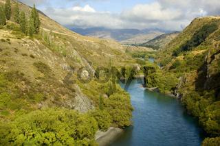 Kawarau Schlucht, der Kawarau Fluss fliesst eine tiefe, von Bergen umgebene Schlucht, hinunter,  Die Gegend um Queenstown wurde fuer viele Filmszenen der 'Herr der Ringe' Triologie benutzt. An diesem Abschnitt des Kawarau wurden die gigantisch wirkenden,