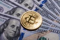 One Bitcoin on hundred dollars bills.
