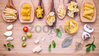 Italian food concept .Various kind of pasta in wooden spoons with ingredients sweet basil ,tomato ,garlic ,parsley ,bay leaves ,pepper ,champignon and parmesan cheese on bamboo cutting board flat lay.