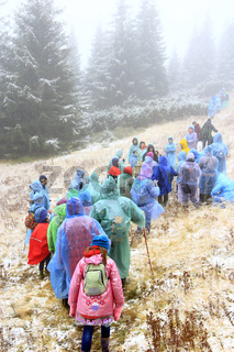 Group of tourists in raincoats on hike in mountains. Travel concept