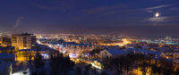 Night winter panorama of a city in a full moon