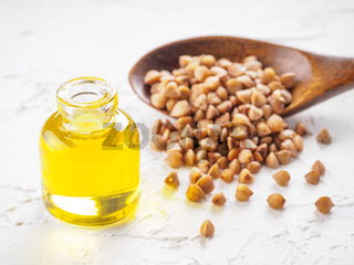 Brown buckwheat in spoon and buckwheat oil close up