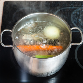 boiling meat broth in stockpot on ceramic cooker
