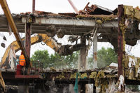 Industrial dismantle, mechanical destruction. Dismantling of the building with the help of heavy hydraulic shears.