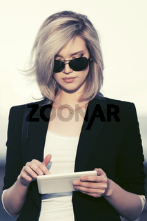 Young fashion business woman in sunglasses using tablet computer in city street