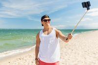 man with smartphone selfie stick on summer beach