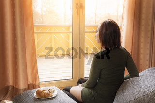 Young relaxed woman looking at the window