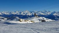 Ski slope on the Diablerets glacier and snow covered mountain ranges. Winter scene in Switzerland.
