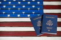 USA passports on glass table over US Flag
