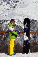 Young snowboarder with helmet in hands and snowboard on viewpoint in winter mountains at sun day