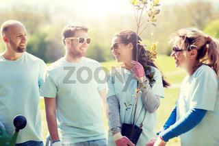 group of volunteers with tree seedling in park