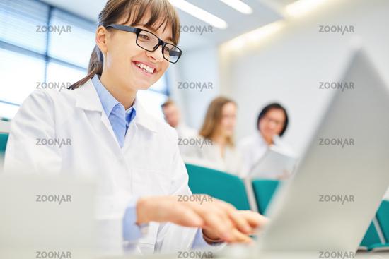 Studentin der Medizin schreibt auf dem Laptop